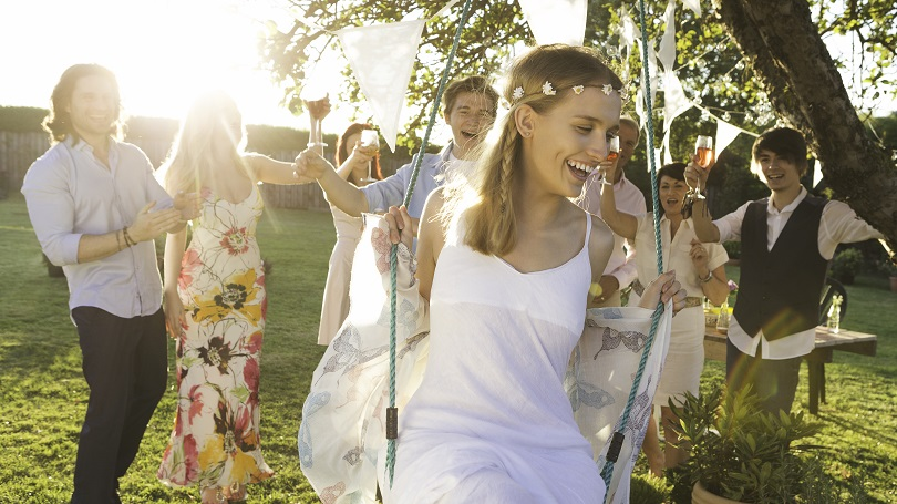 A group of friends and family celebrating at an outdoor wedding reception on a warm summers night. They are all holding up their glasses of wine and toasting the young bride as her husband pushes her on a rope swing.